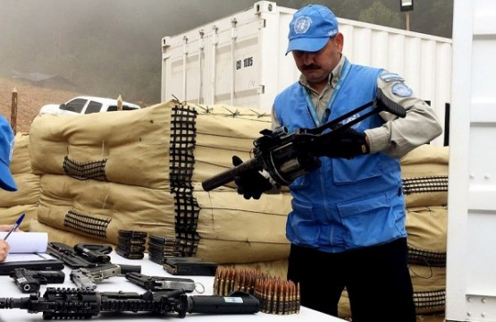 Membro da missão da ONU na Colômbia inspeciona armas entregues pelas Farc. Foto: EFE