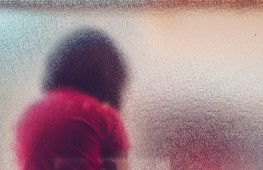 Silhouette of unrecognizable sad autistic girl behind stained glass window